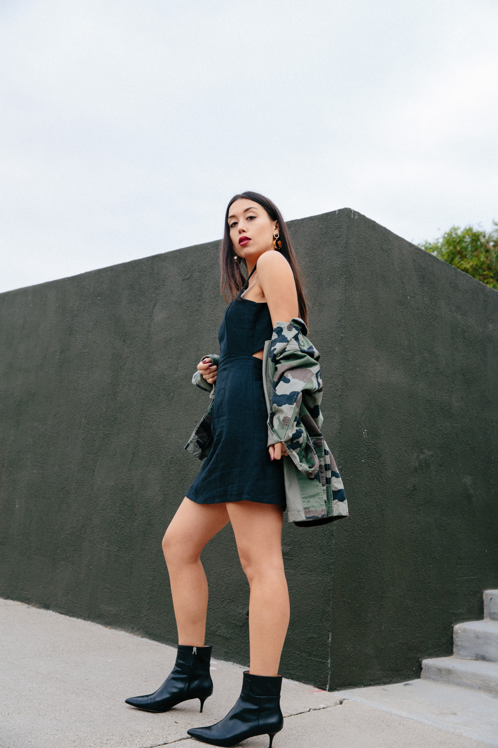 LOVE OR MONEY by Emily Tong wearing black mini dress camo jacket and black kitten boots