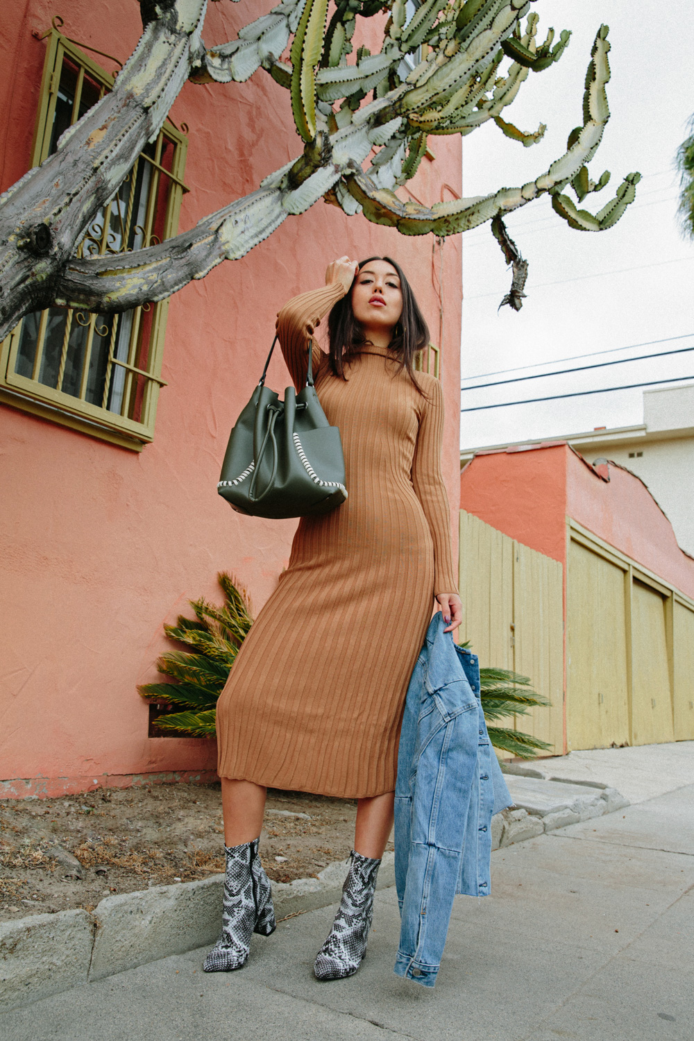 LOVE OR MONEY by Emily Tong wearing camel sweater dress denim jacket and snakeskin boots