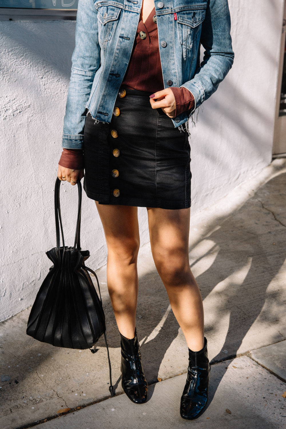 LOVE OR MONEY by Emily Tong wearing Free People button top and button skirt levis jacket and patent boots