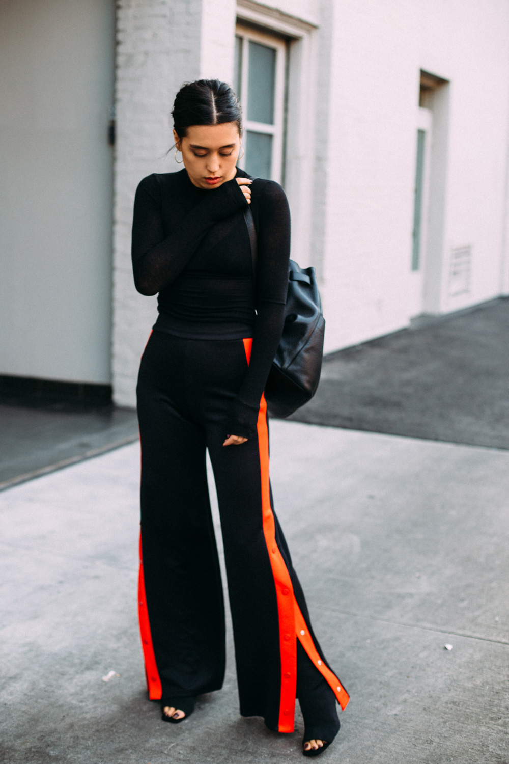 LOVE OR MONEY by Emily Tong wearing red side stripe trousers black crop top and leather backpack