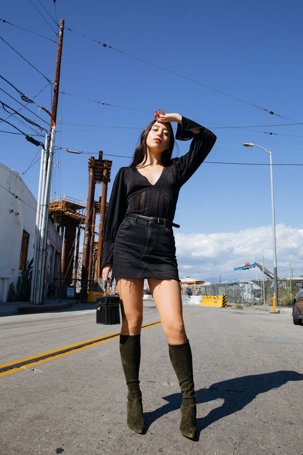 LOVE OR MONEY by Emily Tong wearing black denim mini skirt free people top and manolo blahnik boots
