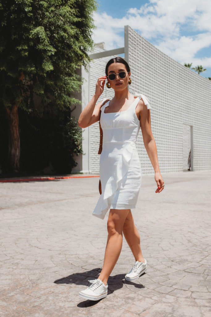 LOVE OR MONEY by Emily Tong wearing white Endless Rose ruffle dress and white Vans in Palm Springs